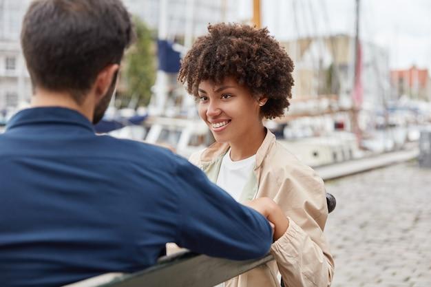 Горизонтальный снимок влюбленной романтической пары, сидящей на скамейке на фоне морского порта, милой беседы