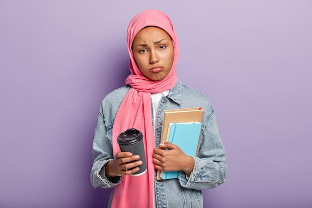 悲しいアラビアの女性の水平方向のショットは、長時間の勉強の後に不快感と疲れを感じます