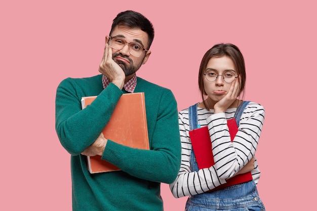 슬픈 유럽 여자와 남자의 가로 샷은 우울한 표정을 지으며 턱을 잡고 문학을 사용합니다.