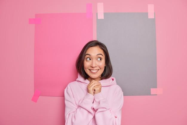 만족한 아시아 여성의 수평 사진은 두 개의 회반죽이 있는 종이로 분홍색 벽에 기대어 즐거운 포즈를 취하는 후드티를 입고 즐겁게 웃고 있습니다.