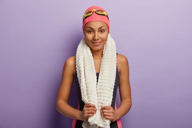 Горизонтальный снимок довольной профессиональной пловчихи с белым полотенцем на шее, посещающей спортивную секцию