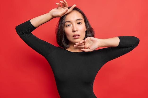 검은 머리를 가진 관능적인 부드러운 아시아 여성의 수평 샷은 카메라를 직접 쳐다보고 선명한 붉은 벽에 검은 점퍼 포즈를 취하는 것은 자연의 아름다움을 가지고 있습니다