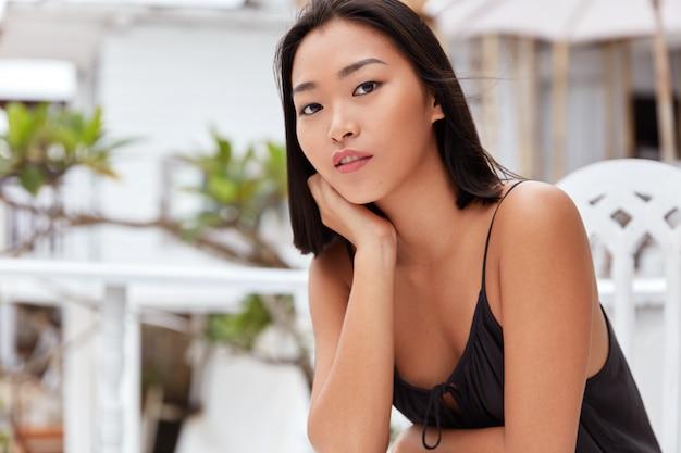 검은 머리, 메이크업 및 건강한 피부를 가진 심각한 매력적인 아시아 젊은 여성 모델의 가로 샷, 테라스 카페 인테리어에 앉아 회의에 늦는 친구를 기다리고 지루함을 느낍니다.