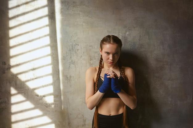 근육질의 슬림 한 몸매와 복싱 경기 전에기도하는 두 개의 긴 머리띠와 심각한 매력적인 젊은 여성 전투기의 수평 샷