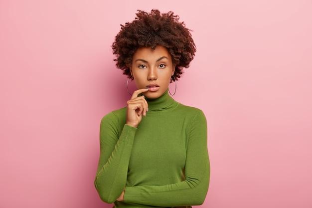 진지한 차분한 어두운 피부의 곱슬 머리 여자의 가로 샷은 둥근 귀걸이, 녹색 터틀넥을 착용하고 손을 부분적으로 가슴 위로 교차 유지하고 똑바로 보이며 분홍색 벽에 모델