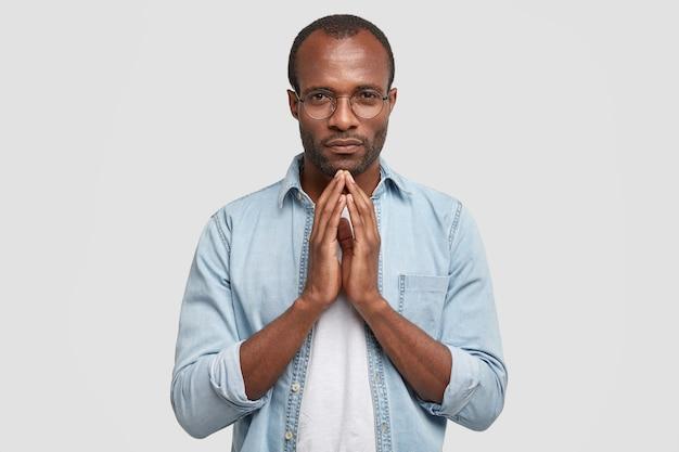 Горизонтальный снимок серьезного темнокожего парня, держащего руки вместе, просит прощения
