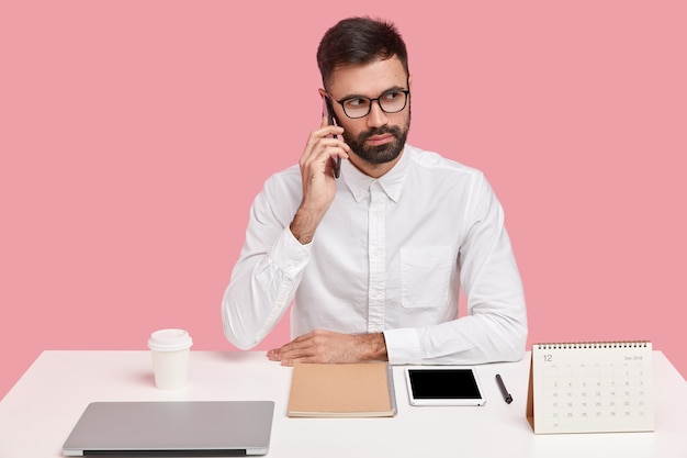 Горизонтальный снимок серьезного предпринимателя с густой щетиной, телефонный разговор, сфокусированный вдаль, одетый в строгую одежду, порядок на столе