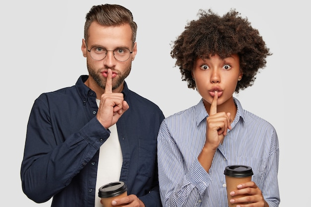 Горизонтальный снимок серьезных женщин и мужчин смешанной расы, держите указательные пальцы над ртом, делая жест молчания