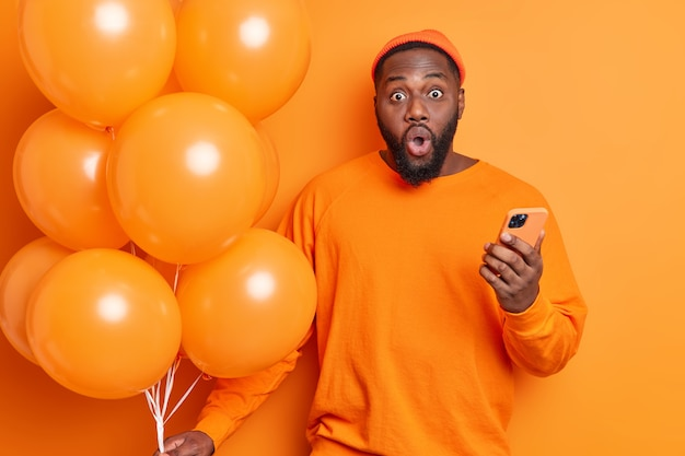 Горизонтальный снимок шокированного бородатого мужчины, удивительно смотрящего в камеру, одетого небрежно, держит мобильный телефон и связку воздушных шаров на вечеринке, изолированную над оранжевой стеной