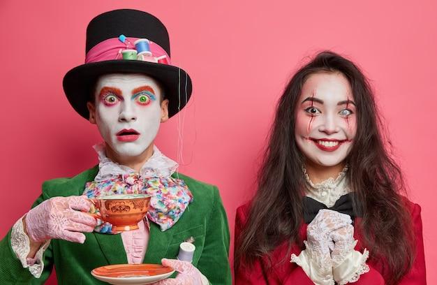 お茶会でカップとショックを受けた男性の帽子屋のポーズの水平方向のショット。幸せなブルネットの女性は顔に不気味な化粧の血の傷を持っています