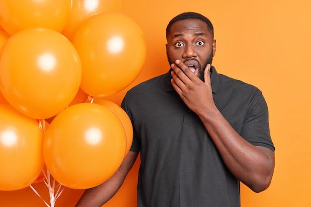 ショックを受けた男の水平方向のショットは、驚いた表情で何かに反応しますあごを着用カジュアルな黒のtシャツはオレンジ色の壁に隔離された膨らんだ風船の束を保持します