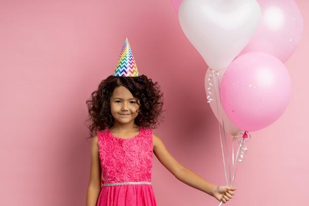Горизонтальный снимок маленькой довольной кудрявой девушки, празднующей день рождения, держащей воздушные шары, красивой платья и яркой шляпы, улыбающейся. концепция счастливого детства.