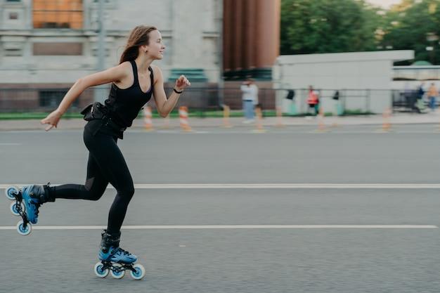 Горизонтальный снимок энергичной спортивной женщины, которая любит кататься на роликах, ее фотографируют в движущихся позах на дороге на размытом уличном фоне, регулярно занимаются фитнесом для поддержания формы и здоровья.