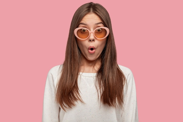 Горизонтальный снимок ошеломленной гламурной молодой женщины с шокированным выражением лица