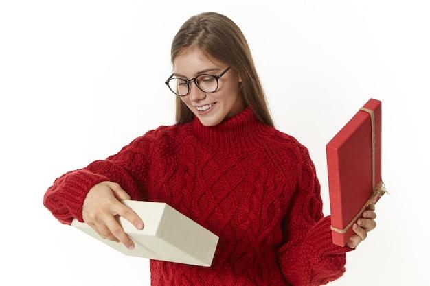 안경과 니트 스웨터에 세련된 즐거운 젊은 백인 여자의 가로 샷 크리스마스 선물을받는 동안 행복한 표정을 짓고 선물 상자를 열고 광범위하게 웃고