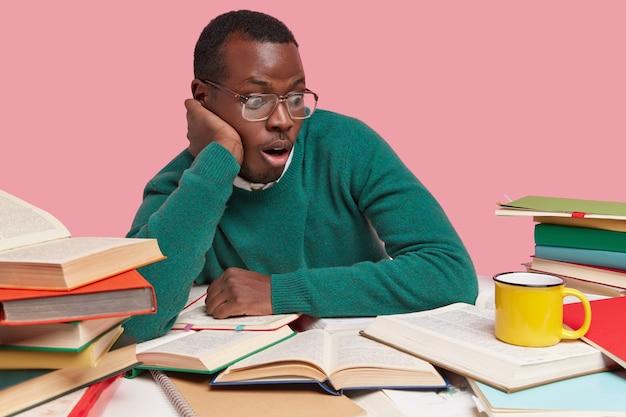 놀란 어두운 피부 남자의 가로 샷은 열린 교과서에서 겁 먹은 표정으로 초점을 맞춘 광학 안경을 착용합니다.