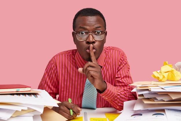 Горизонтальный снимок удивленного темнокожего молодого человека, который жестикулирует, держит ручку, одет в строгую рубашку и просит не распространять личную информацию.