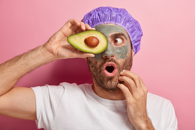 Горизонтальный снимок удивленного европейца с открытым от удивления ртом, прикрывающего глаз ломтиком авокадо, одетого в повседневную одежду и шапочку для душа