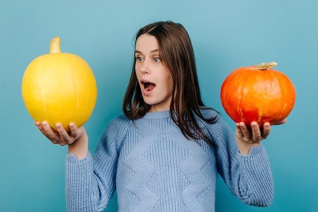 Горизонтальный снимок удивленной впечатленной молодой женщины, удивительно смотрящей на оранжевую тыкву