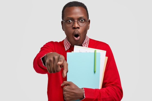 Горизонтальный снимок удивленного испуганного чернокожего мужчины, указывающего на камеру, открывающего рот от шока, близко несущего учебники, в круглых очках