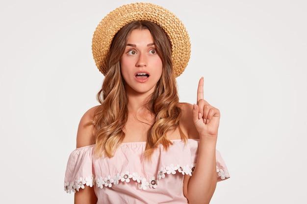 Горизонтальная съемка удивленной молодой европейской женщины с приятной внешностью, длинными волосами, носит летнюю шляпу, блузку, указывает указательным пальцем вверх, стоит на белом. посмотри наверх