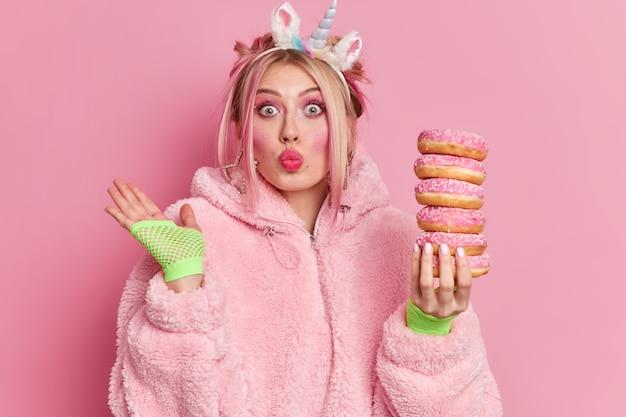驚いた若い女性の水平方向のショットは明るい化粧をして唇を丸く保ち、手を上げてドーナツの山を保持します