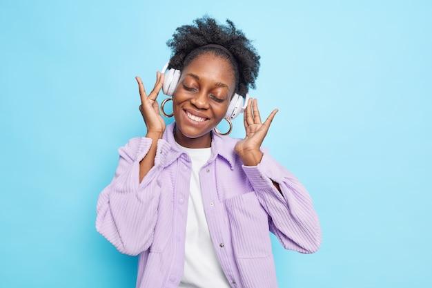 10대 소녀의 수평 샷은 검은 피부의 자연스러운 곱슬머리를 가지고 있으며 기쁨으로 눈을 감고 헤드폰을 통해 음악을 듣습니다.