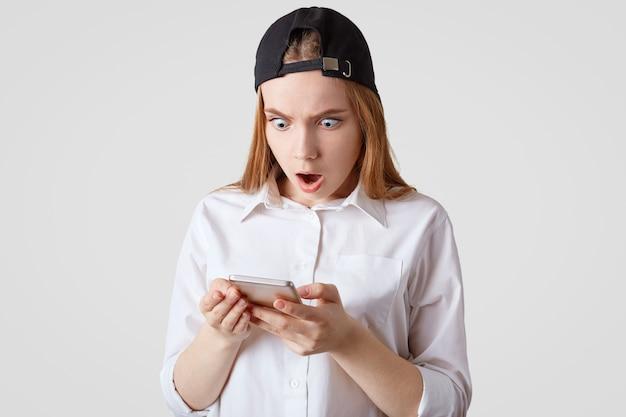 거친 모자와 셔츠에 십 대 소녀의 가로 샷, 스마트 폰을 보유하고 흰 벽을 통해 격리 된 스마트 폰에 예기치 않은 메시지를 수신 사람, 기술 및 인간의 반응