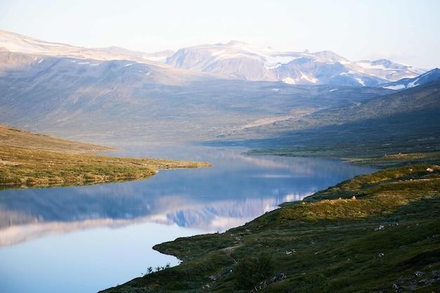 잔잔한 호수, 녹색 땅과 산의 아름다운 전망의 가로 샷