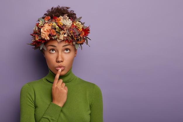 思いやりのある暗い肌の女性の水平方向のショットは、悲しげな表情をしていて、上に焦点を合わせ、唇に指を置き、秋の植物で作られた美しい花輪を着て、物思いにふける表情をして、正しい決断をしようとします