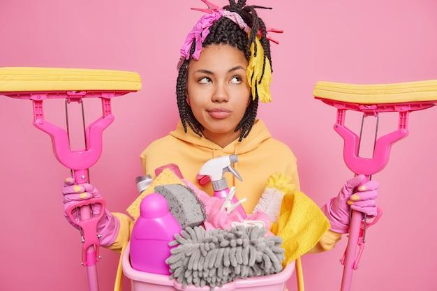 Горизонтальный снимок задумчивой домохозяйки в защитных резиновых перчатках и толстовке с двумя швабрами.
