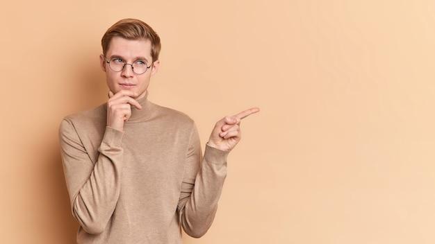 사려 깊은 젊은이의 가로 샷은 턱을 잡고 제안 된 제안 포인트에 대해 생각하고 광고 콘텐츠를위한 복사 공간을 보여줍니다. 둥근 안경 캐주얼 점퍼를 착용합니다.