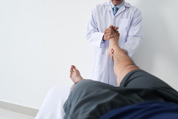 발 관절 조작을 하는 다리를 잡고 있는 남성 환자와 함께 일하는 알아볼 수 없는 정골 의사의 수평 샷