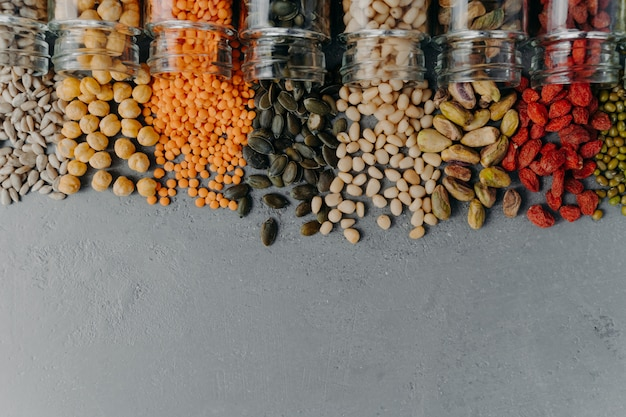 Горизонтальная съемка различных разноцветных зерен, пролитых из стеклянных бутылок