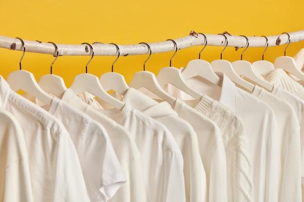 黄色の背景の上に分離された、ラックにぶら下がっている白い婦人服の水平方向のショット。女性の衣装を着た楽屋。