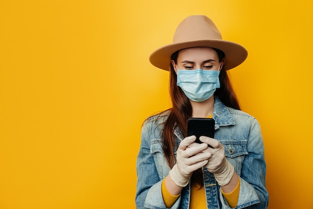 医療用滅菌フェイスマスクグローブを着用した女性の水平方向のショット、友人とのオンラインチャット、電子メールで受信した通知の確認、常に連絡を取り合う、デニムジャケットの着用。パンデミックコロナウイルスの概念