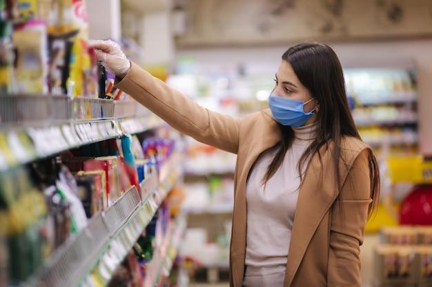 保護マスクと手袋の女性の水平方向のショットは、商品の価格でラベルを読んでいます