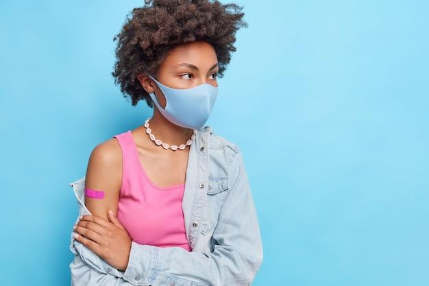 Горизонтальный снимок женщины с вьющимися волосами в защитной маске с вакцинированной рукой, сфокусированной вдали, в джинсовой рубашке, изолированной над синей стеной