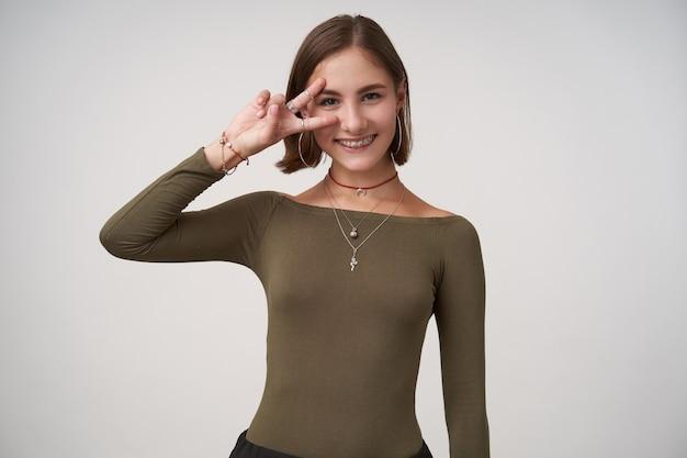 短いヘアカットで若い魅力的なブルネットの女性の水平方向のショットは、正面に勝利の兆候を示し、白い壁の上に立って元気に嗅ぎます
