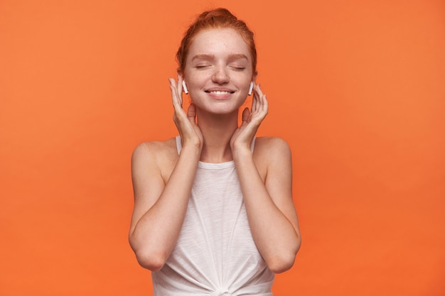 매듭에 캐주얼 옷을 입고 빨간 머리를 가진 젊은 매력적인 여자의 가로 샷, 닫힌 눈으로 그녀가 좋아하는 노래를 즐기고, 오렌지 배경 위에 절연 이어폰에 손을 유지