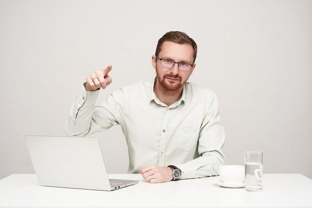 白い背景の上に座って、人差し指でカメラを指して手を上げたまま眼鏡をかけた若いひげを生やした短い髪の男性の水平方向のショット