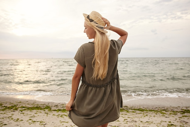 ボートの帽子に手を上げて、背中で海辺でポーズをとっている間、喜んで笑っている若い魅力的な長い髪のブロンドの女性の水平方向のショット