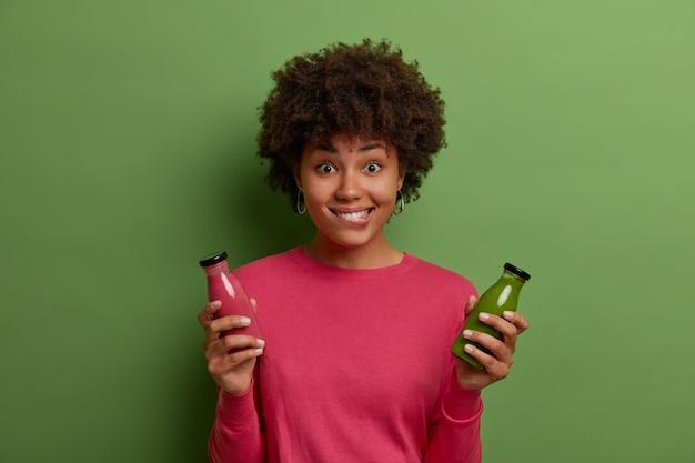 젊은 어두운 피부 여자의 가로 샷 녹색 야채와 분홍색 과일 스무디를 마신다, 입술을 물고, 건강한 식생활 라이프 스타일을 가지고 있으며, 캐주얼 점퍼에 실내 포즈. 체중 감소, 적절한 영양