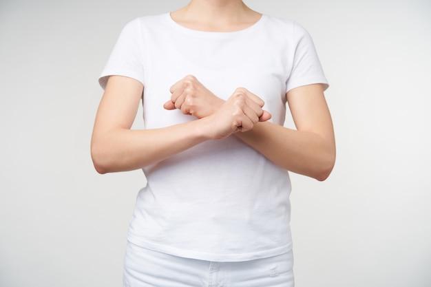 手話で彼女の考えを表現しながら手を交差させている若い色白の女性の水平方向のショット、つまり白い背景の上に立っている間単語の休息を意味します