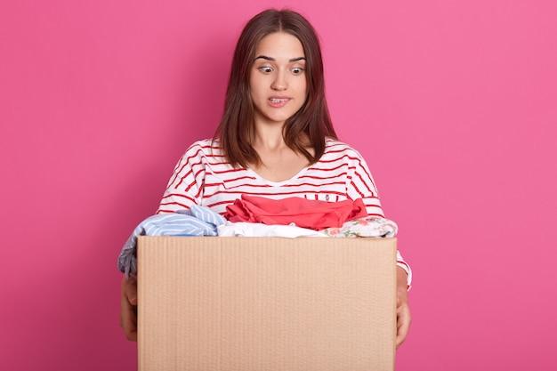 Горизонтальный выстрел молодого волонтера стоит с картонной коробкой, полной подаренной одежды, очаровательная женщина смотрит на одежду с испуганным выражением лица, кусает ее низкую губу, дама в полосатой повседневной рубашке.