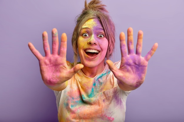 Horizontal shot of optimistic joyful young girl shows two colorful palms, celebrates holi festival, laughs gladfully, plays with special colored powder. focus on painted hands. splash of color