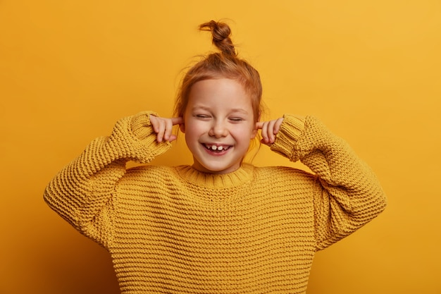 Horizontal shot of optimistic merry small kid plugs ears with index fingers, chuckles positively, has ginger hair bun, wears oversized knitted sweater, isolated on yellow wall. stop this sound