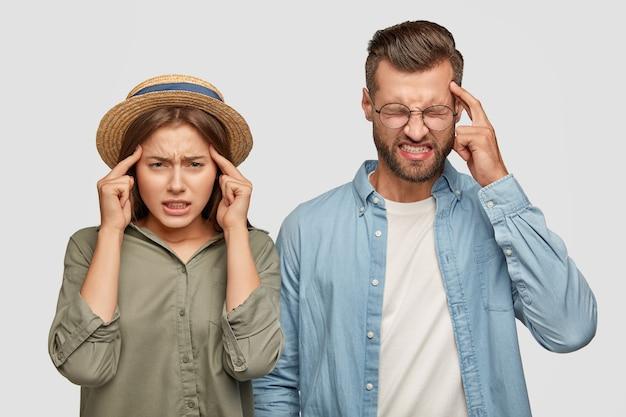 Inquadratura orizzontale di colleghi stanchi oberati di lavoro tengono l'indice sulle tempie, soffrono di mal di testa