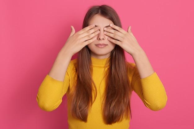 Colpo orizzontale di bello giovane modello sveglio bello pacifico che sta isolato sopra la parete rosa in studio, coprendo gli occhi di mani, indossando la felpa gialla, essendo solo. concetto di sorpresa.