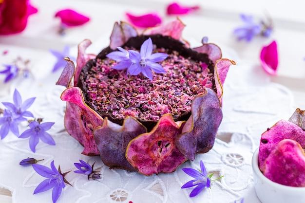 Inquadratura orizzontale di una torta viola vegana cruda di pere con pere disidratate su un tavolo bianco